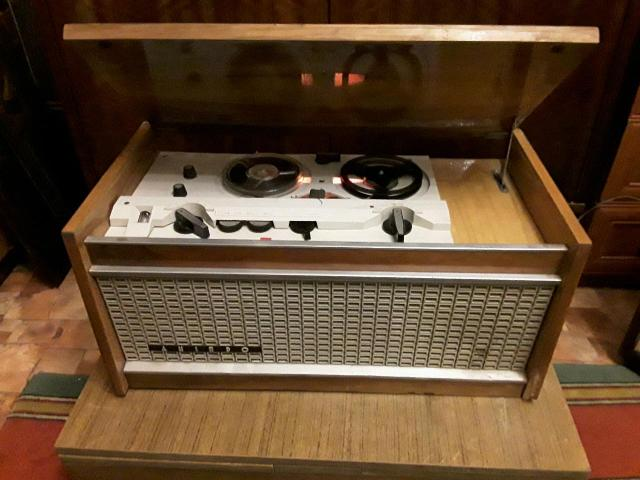 """Ламповый Катушечный Магнитофон """"Днiпро-14А"""" 1970 года.Киев,завод""""Маяк"""". В рабочем состоянии. Магнитофон расчитан на двухдорожечную запись, скорость движения магнитной ленты """"9"""" и """"4"""" см/сек. Катушки № 15 на 250 м. Выходная мощность 15 Вт. Звук громкий и отчетливый. Раздельная регулировка тембров по НЧ и ВЧ. Питание от 127 или 220 вольт. Размеры магнитофона - д620 х в290 х г320 мм, вес 18 кг. В магнитофоне имеется кнопка наложения записи, кнопка паузы. 3 двигателя, ведущий и два перемоточных.Подшипник ведущего надо смазать, скрипит временами. Схема магнитофона на семи лампах включая и оптический индикатор. В корпусе 4 громкоговорителя, ( 2спереди и 2 по бокам). Есть царапины лакового покрытия на крышке,и небольшой скол внизу, справа.В комплекте 3 катушки с записями 60ых годов +пустышка."""