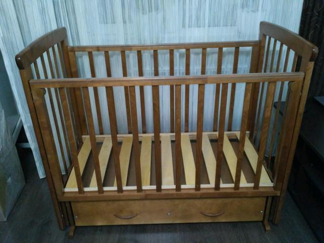 Детская кроватка изготовленная Можгинским лесокомбинатом из массива березы. Снабжена маятниковым механизмом с полностью бесшумным ходом. Высота основания может быть изменена (3 уровня ложа), подвижная стенка снабжена двумя съемными деталями и опускается. При желании ограждение можно снять, чтобы ребенок мог ложиться спать самостоятельно. Без матраса. Размер матраса в кроватку 1200*600см
