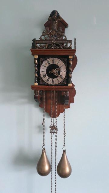 Заански настенные часы с боем!! Голландия! Часы этого типа выпускались Голландской школой мастеров ещё с конца 17 века. Данные часы были выпущены в 70-х годах 20-го века в Голландии. Часы выполнены из дерева. Красивый циферблат с римскими/арабскими цифрами на шкале и четырьмя ангелами в каждом углу. Маятниковые часы работают и бьют каждый час. Механизм на уверенном ходу. Снизу часов движется латунный маятник в отображении скачущего всадника на лошади. Размер часов: 55х23х15см. Часы в хорошей для возраста сохранности!